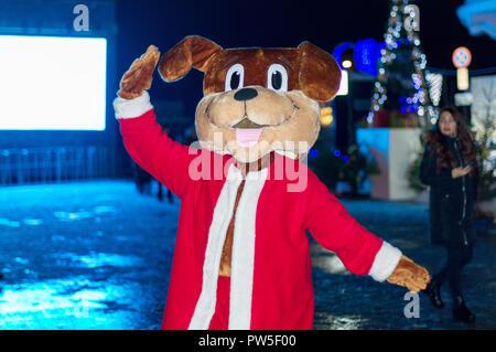 Ein junges Mädchen in einem Hund Kostüm auf der Straße, ist mit Besucher fotografiert und feiert das neue Jahr von Russland. - Stockfoto