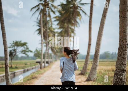 Eine Frau lief im seitlichen Kokospalmen - Stockfoto