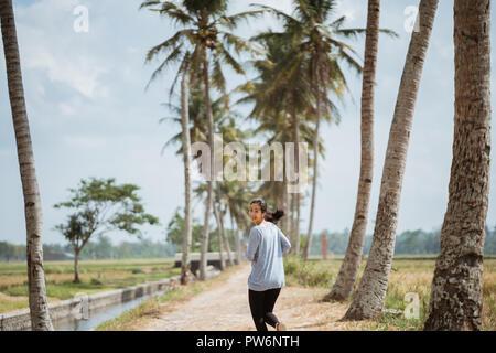 Eine Frau lief in der Kokospalmen, zurück an die Kamera suchen - Stockfoto