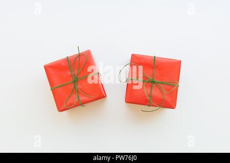 Zwei Geschenkboxen in rot Papier mit Green Ribbon Band umwickelt. Weißer Hintergrund. Urlaub Silvester Weihnachten corporate präsentiert Shopping Verkauf. Plakat Verbot - Stockfoto