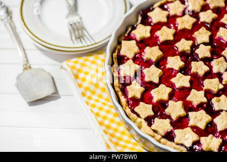 Scheibe der köstlichen hausgemachten Sour Cherry Pie an der Platte. Schüssel mit Schlagsahne, Dessert gabeln und die ganze Torte auf Holztisch, klassisches Rezept, Ansicht von - Stockfoto