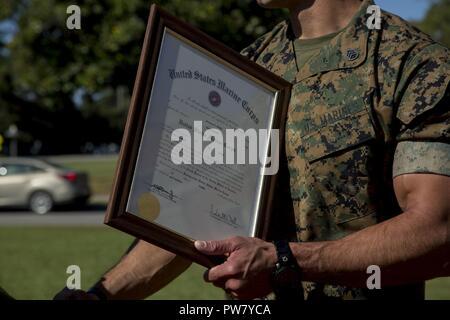 Us Marine Corps Staff Sgt. Jeramey D. Mielke ist seine Förderung rechtfertigen von Generalmajor John K. Liebe gegeben, Kommandierender General, 2nd Marine Division, während seiner Promotion am Camp Lejeune, N.C., Oktober 2, 2017. Mielke wurde von Sergeant zu Staff Sergeant von Generalmajor John K. Liebe gefördert. - Stockfoto