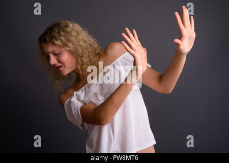 Junge schöne Frau mit blond gelocktem Haar gegen Grau backgro - Stockfoto