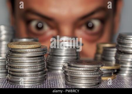 Fokus auf Münze. Ein reichhaltiges gierig älterer Mann schaut auf Münzen. Der Kollektor sieht seinen Reichtum. Ein älterer Mann in Metall Geld starrte auf den Boden. - Stockfoto