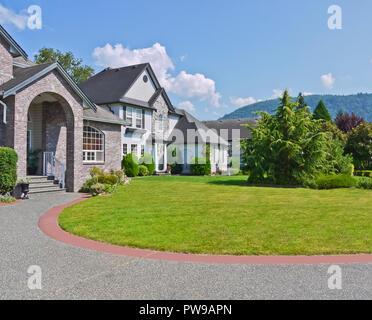 Abgerundet Auffahrt und Rasen vor Wohnhäusern auf blauen Himmel Hintergrund. Luxuriöse Einfamilienhäuser mit gepflegten Vorgärten und auf die Berge - Stockfoto