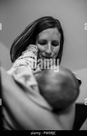 Monochromes Bild der jungen Mutter liebevoll halten Ihr Baby und spielen mit ihren kleinen Hand.
