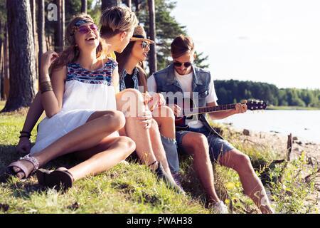 Gruppe von Freunden feiern und Musik hören bei Sonnenuntergang - Stockfoto