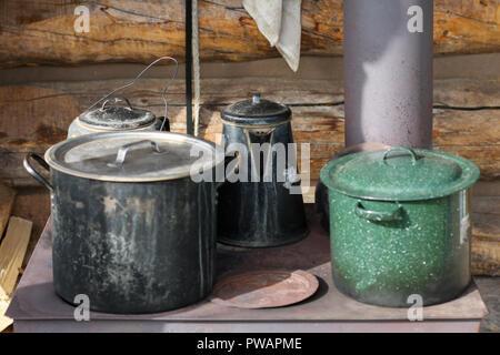 Yukon, Alaska. Nahaufnahme von Töpfen und Pfannen in einem alten Bügeleisen Herd in der Außenseite der Kabine platziert. - Stockfoto