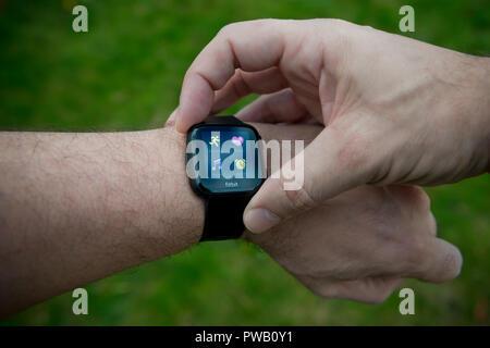 Ein Männer umgekehrt Aktivität überprüft seine Fitbit tracker Einschließlich Herzfrequenzsensor mit BPM-Einheiten während einer Übung Training überwachen. - Stockfoto