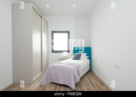 Kleines Schlafzimmer mit einem Bett, einem Kleiderschrank mit ...