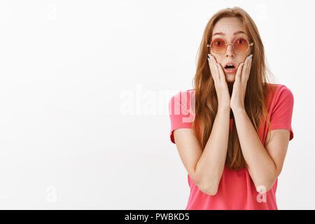 Studio geschossen von schockiert und beeindruckt bezaubernde Rothaarige Mädchen mit Sommersprossen mit den letzten Nachrichten Keuchen öffnen Mund, Hände auf Gesicht an der Kamera gerichtet Überrascht starrte fassungslos - Stockfoto