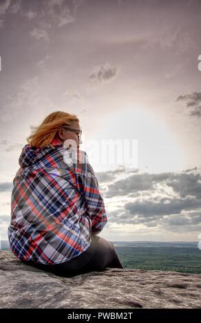 Junge Frau in gestreifte Jacke einen Rest auf felsigen Gipfel über dem Wald Tal. Frühling sonniges Wetter mit warmen Farben. - Stockfoto