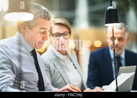 Reifen Geschäftsmann lesen Schreibarbeiten während einer Sitzung mit zwei Kollegen während sitzen zusammen an einem Tisch in einem modernen Büro - Stockfoto
