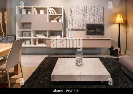 Modernes Wohnzimmer mit Esstisch offen zu einem Wohnbereich mit Bücherregal, Fernsehen, Couchtisch und Sofa von einem ständigen Co beleuchtet - Stockfoto