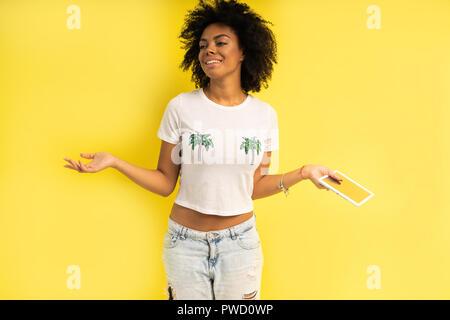 Hübsche junge afro-amerikanische Frau stehen und mit Tablet-PC auf gelben Hintergrund. - Stockfoto