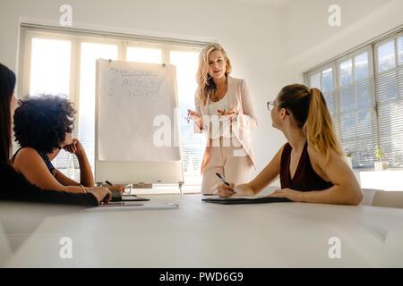 Weibliche manager diskutieren über Budget und Einkommen mit Kollegen während einer Vorstandssitzung. Gruppe von Unternehmerinnen in Meetings über Finanzen. - Stockfoto