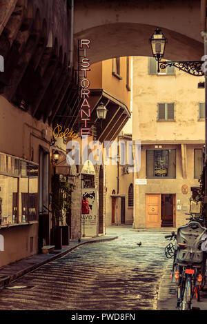 Eine Seitenstraße in Florenz, Italien, Jahrgang angezeigt, bis Sie die Neon ristornate unterzeichnen und den Kindersitz auf dem Fahrrad sehen. - Stockfoto
