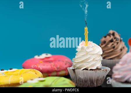 Party mit frischen Muffins und bunten iced Ring Donuts über einen blauen Hintergrund mit Kopie Raum - Stockfoto
