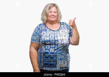 Senior Plus size kaukasische Frau über isolierte Hintergrund lächelnd mit glücklichen Gesicht und zeigt auf die Seite mit dem Daumen nach oben. - Stockfoto