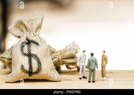 Finanzielle Investitionen Verhandlung, Diskussion unter den CEO oder Konzept ausführen: Miniatur Figur drei Unternehmer über Geld reden investieren Vertrag agr - Stockfoto