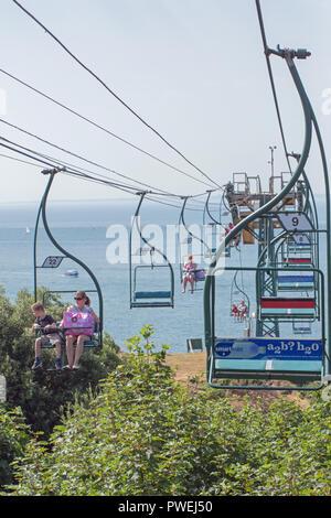 People auf dem Sessellift mit Blick auf Alum Bay, und die Nadeln, Isle of Wight. Hampshire. Southern England. Die UK. Leere Sitze, besetzten Sitze. Sommer. - Stockfoto