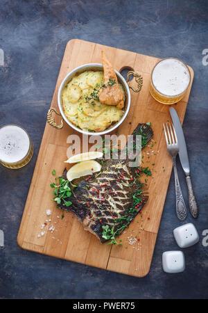 Köstliche gebackene Scholle mit Kartoffelgratin und Bier, Ansicht von oben. - Stockfoto