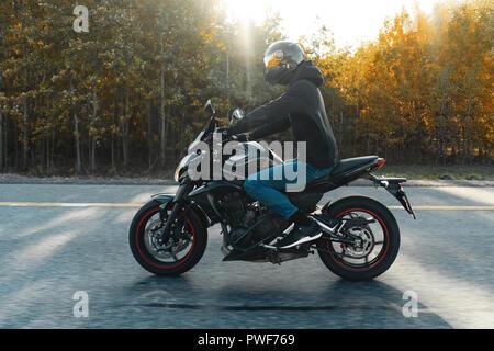 Treiber reiten Motorrad auf leere Straße im schönen Herbst Wald. - Stockfoto