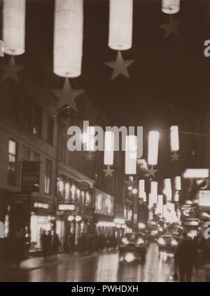 Weihnachten in den 1930er Jahren. Die belebte Straße Regeringsgatan mit Weihnachtsbeleuchtung dekoriert ist. Das elektrische Licht und die Weihnachtsdekorationen schafft eine schöne Weihnachten. Schweden 1930 - Stockfoto