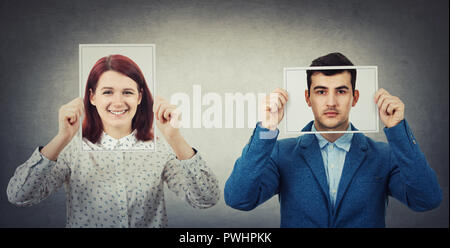 Kaufmann und Frau für ihre Gesichter mit Photo Blätter mit glücklich und traurig portrait Emoticon, wie eine Maske die echten Emotionen aus der Gesellschaft zu verstecken. - Stockfoto