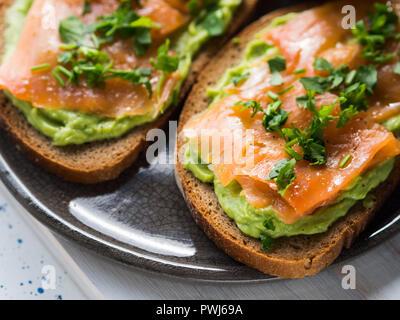 Roggen Brot Toast Avocado mit Räucherlachs auf weißem Holzbrett - Stockfoto