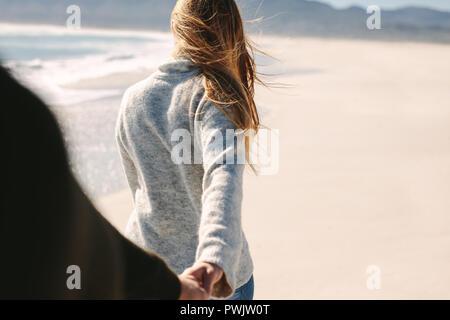 Die Frau mit Freund Hand beim Spaziergang am Strand. Junges Paar zu Fuß am Strand entlang. POV des Menschen folgenden Freundin gehen. - Stockfoto