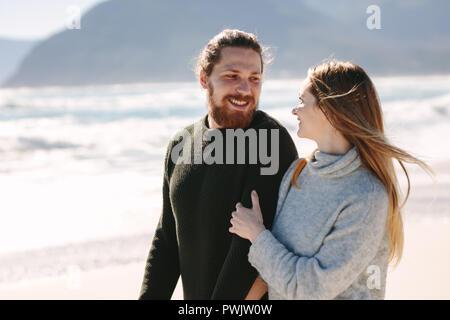 Schöner Mann zu Fuß mit seiner Freundin am Strand. Junges Paar zusammen entlang der Küste. - Stockfoto