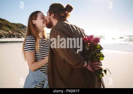 Freund Holding überraschung Blumenstrauß für Freundin am Strand. Romantisches Paar auf ein romantisches Date am Strand. - Stockfoto