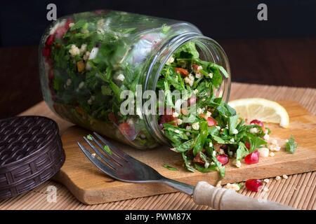 Hirse taboule in einem Glas mit Granatapfel Samen, Petersilie und Minze - Stockfoto