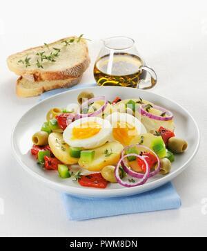 Warmer Kartoffelsalat mit Paprika, Oliven, Zwiebeln und ein weich gekochtes Ei - Stockfoto