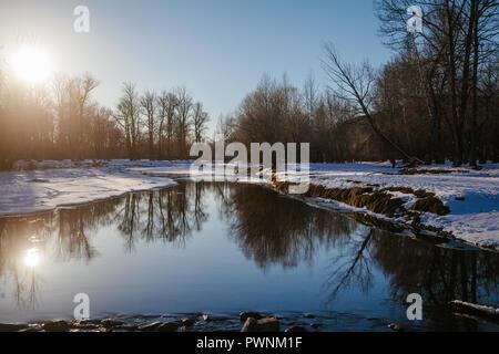 Landschaft mit der hellen Sonne scheint durch die Bäume auf einem neu aufgetaut Fluss, der Bäume und der blaue Himmel spiegelt. Arkhangai, Mongolei - Stockfoto