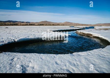 Mongolische Landschaft mit frisch aufgetauten Fluss Anfang durch den Schnee und Eis zu fließen. Feder. Arkhangai, Mongolei - Stockfoto