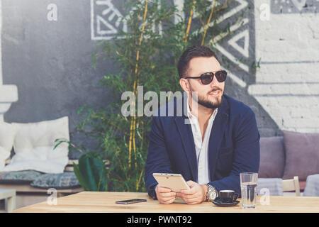 Portrait von stattlichen Geschäftsmann Holding digitale Tablette im Cafe. - Stockfoto