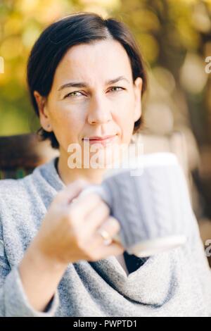 Frau mit warmem Strick Kleidung trinken eine Tasse heißen Tee oder Kaffee im Freien bei Sonnenlicht - Saison, Freizeit und Personen Konzept - schöner Morgen - Stockfoto