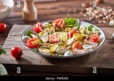 Frische hausgemachte Salate mit natürlichen Zutaten - organische sauber Gemüse, Hähnchen Fleisch und guail Eier, würzigen Senf in einer Platte auf einem Holzbrett. - Stockfoto