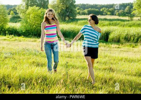 Frau mit Tochter jugendlich Wandern in der Natur halten sich an den Händen. Hintergrund blauer Himmel, grünes Gras, kleinen Fluss. - Stockfoto