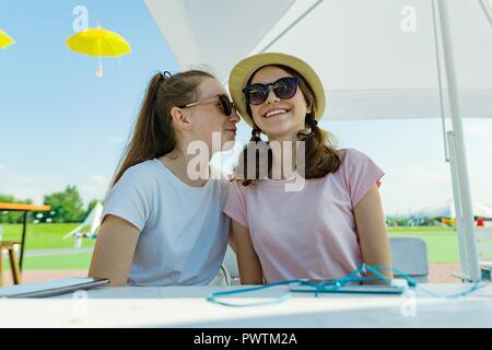 Mädchen jugendliche Spaß haben, Reden, Geheimnis, Lachen. In einem Straßencafe sitzen, sonnigen Sommertag in der Erholung und Unterhaltung - Stockfoto