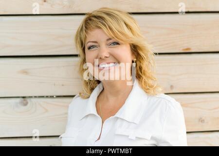 Portrait positive reife Frau mittleren Alters in der Nähe lächelnd. Blonde Frau, outdoor Holz- Hintergrund. - Stockfoto