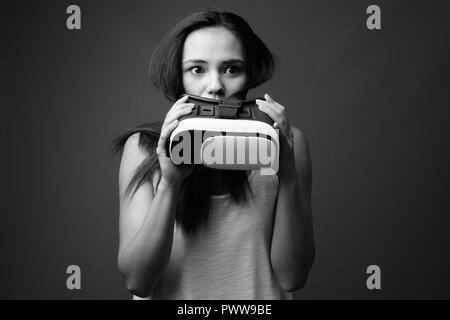 Junge asiatische Frau gegen grauen Hintergrund in Schwarz und Weiß - Stockfoto