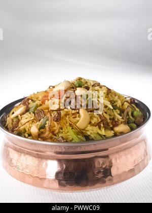 Pflanzliche BIRYANI SERVIERT IN EINEM KUPFER HANDI. Es ist AUS MIT REIS UND gemischtem Gemüse geschnürt mit Masala und garniert mit Nüssen und Rosinen - Stockfoto