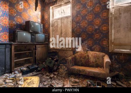 Innenansicht eines Zimmer mit alten Möbeln und Fernseher in einem verlassenen Schloss in Belgien. - Stockfoto