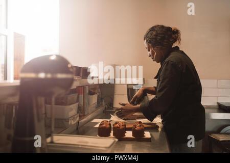 Bäcker schneiden Brownies an der Theke einer gewerblichen Küche - Stockfoto