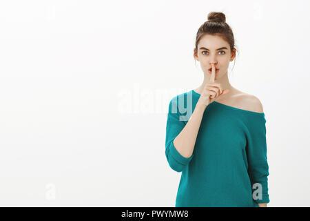 Shh, behalten Sie dieses Geheimnis von jedermann. Portrait von weiblichen stilvolle Frau in Lose grünen Pullover, psst Geste mit dem Zeigefinger über Mund, falten Lippen, fragt ruhig hält, oder Schweigen - Stockfoto