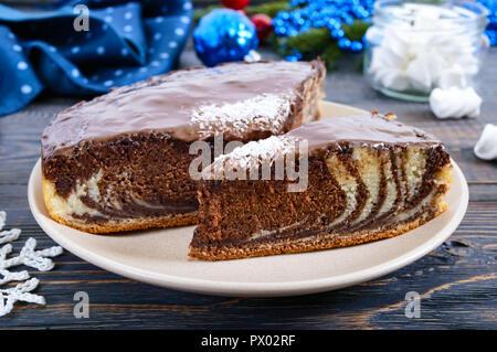 Ein Stück leckeren Kuchen mit zwei Farben Schokolade und Kokos Chips. Festliche Kuchen. - Stockfoto