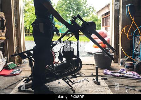 Mechanikerin Reparatur Motorrad in einer Garage.